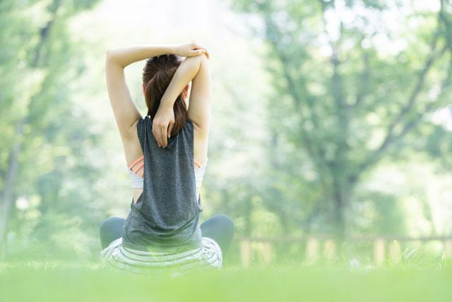 森の中で朝日を浴びている女性